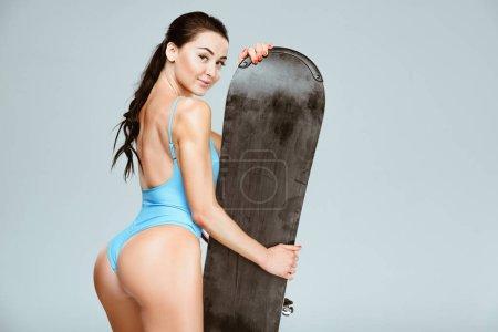 Photo pour Vue arrière du surfeur sexy en maillot de bain bleu posant avec snowboard isolé sur fond gris - image libre de droit