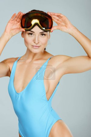 sexy sportswoman in blue swimwear wearing ski goggles isolated on grey