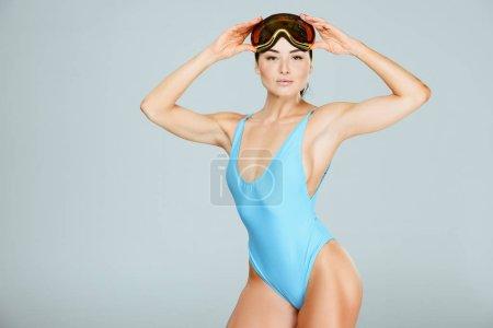 seductive sportswoman in blue leotard wearing ski goggles isolated on grey