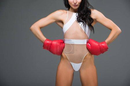 Photo pour Image recadrée de femme sportive sexy en justaucorps blanc et gants de boxe debout avec les mains akimbo isolé sur gris - image libre de droit