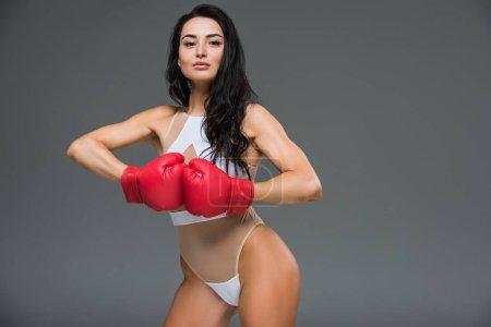 Photo pour Sexy femme sportive en justaucorps blanc montrant les mains en gants de boxe isolé sur gris - image libre de droit