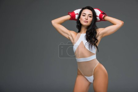 Photo for Sexy sportive woman in white leotard and boxing gloves standing with hands above head isolated on grey - Royalty Free Image
