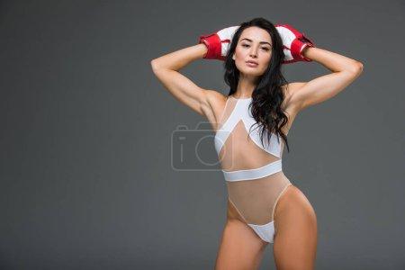 Photo pour Sexy femme sportive en justaucorps blanc et gants de boxe debout avec les mains au-dessus de la tête isolé sur gris - image libre de droit