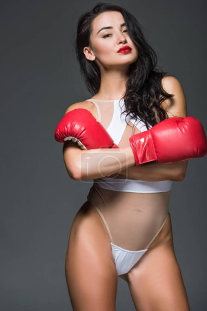 attractive sportive woman in white leotard and boxing gloves standing with crossed arms isolated on grey