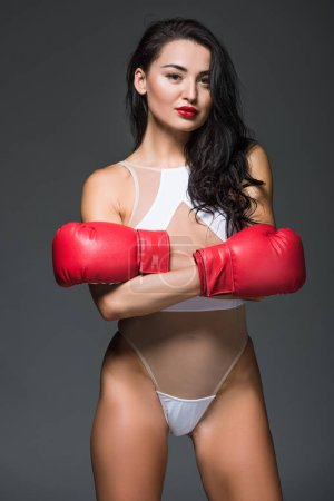 sexy sportive woman in white sportswear and boxing gloves standing with crossed arms isolated on grey