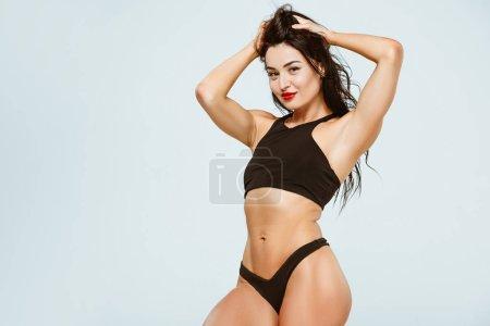 Photo pour Femme sexy en soutien-gorge de sport et culotte toucher les cheveux et en regardant la caméra isolée sur gris - image libre de droit