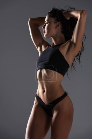 Photo for Sexy woman in sport bra and panties touching hair and looking away isolated on grey - Royalty Free Image