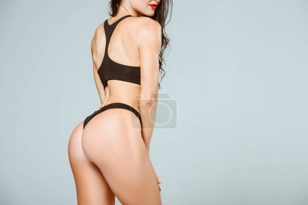 Photo for Cropped image of sexy woman posing in sport bra and panties isolated on grey - Royalty Free Image