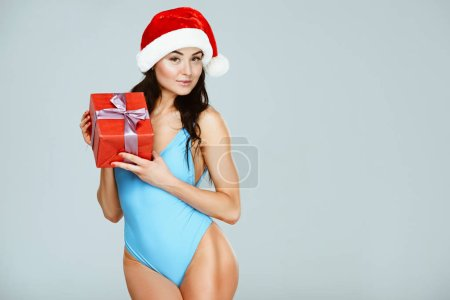attractive sportive woman in blue swimwear and christmas hat holding present isolated on grey