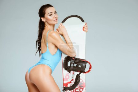 side view of sexy sportswoman in blue swimwear leaning on snowboard isolated on grey