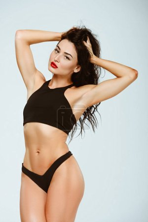 Photo for Sexy woman in sport bra and panties touching hair isolated on grey - Royalty Free Image