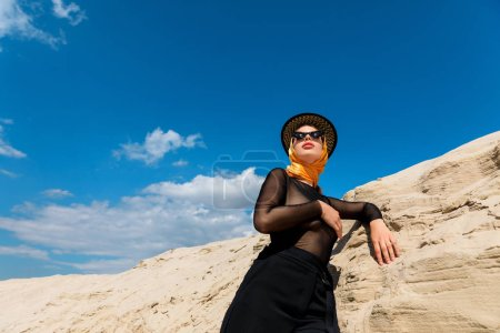 bottom view of elegant woman posing near sand dune with blue sky on background
