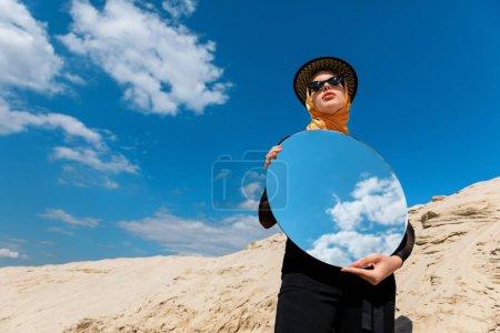 stilvolles attraktives Mädchen posiert mit rundem Spiegel und Reflexion des bewölkten Himmels