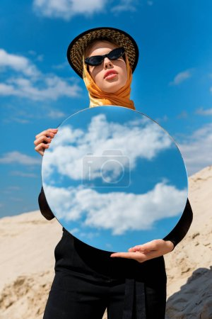 fashionable attractive girl posing with round mirror and reflection of cloudy sky