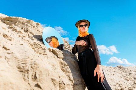 stylish beautiful woman posing near sand dune with mirror