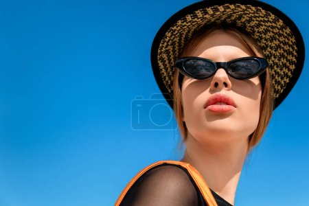portrait of fashionable woman in trendy sunglasses and hat, blue sky on background