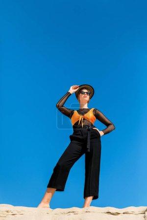 Photo pour Vue du dessous de la belle femme à la mode, posant avec un ciel bleu sur fond - image libre de droit