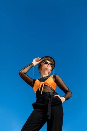 Photo pour Vue de dessous de femme qui pose en mode lunettes de soleil et chapeau élégant, ciel bleu sur fond - image libre de droit