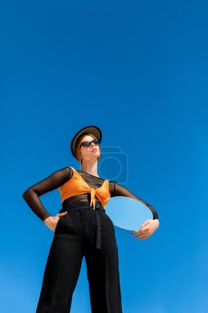 bottom view of fashionable girl posing with round mirror, blue sky on background