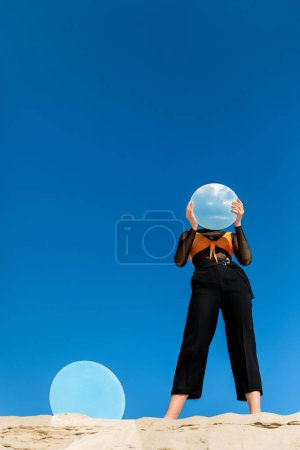 fashionable model holding mirror with reflection of sky in front of the face