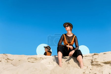fashionable model posing on sand with round mirrors with reflection of blue sky
