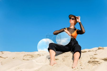 stylish model posing on dune with round mirrors with reflection of blue sky