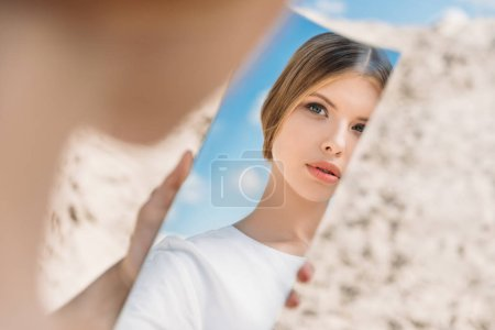 beautiful girl holding piece of mirror and looking on her reflection
