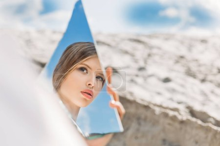 charming girl holding piece of mirror and looking on her reflection
