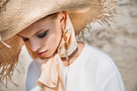 beautiful tender girl posing in silk scarf and straw hat