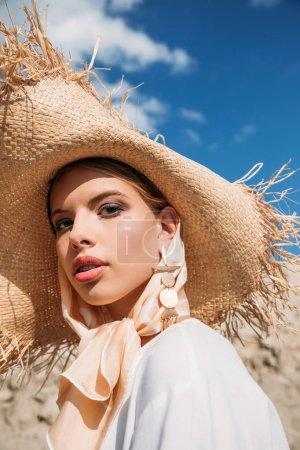 beautiful stylish girl posing in trendy silk scarf and straw hat