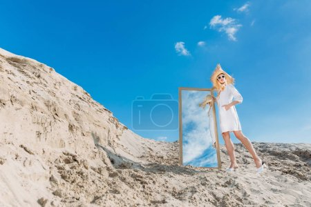 fashionable girl posing in white clothes and straw hat near mirror on sand dune