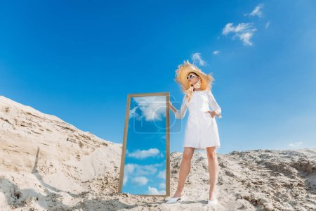 stylish model posing in white clothes and straw hat near mirror on sand dune