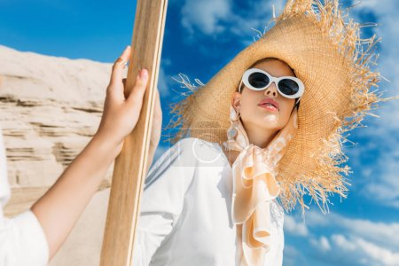 stylish girl in sunglasses, scarf and straw hat looking at her reflection in mirror