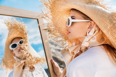 beautiful girl posing in sunglasses, white clothes and straw hat near mirror