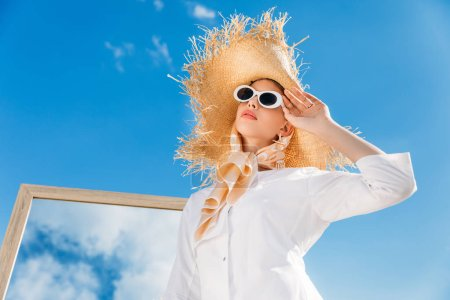 stylish girl posing in sunglasses, white clothes, scarf and straw hat near mirror on sunny day