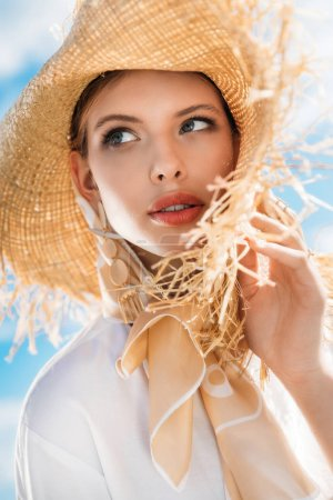 charming young woman posing in silk scarf and straw hat