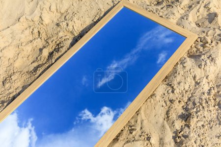 mirror with reflection of blue cloudy sky lying on sand