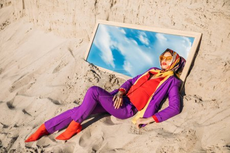 beautiful model in fashionable clothes lying on mirror with reflection on cloudy sky