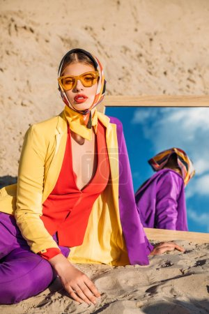 beautiful model in colorful fashionable clothes posing near mirror on sand dune