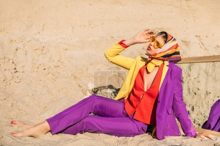 beautiful girl in colorful elegant clothes sitting on sand with mirror