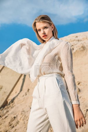 attractive blonde model with white silk scarf posing in desert