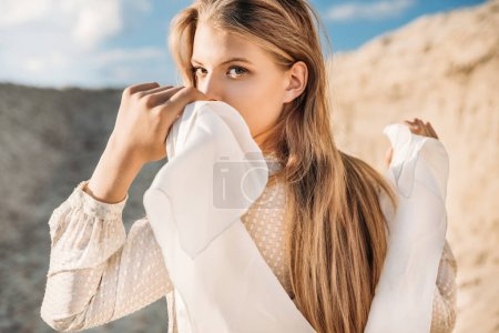 beautiful blonde girl with white scarf walking on sand dune