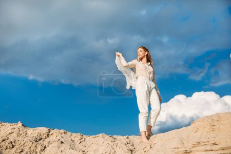 charming fashionable model in white trendy clothes with silk scarf walking on sand dune