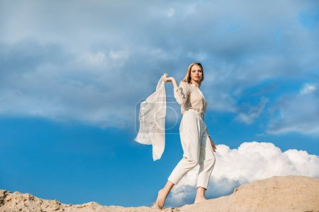beautiful fashionable girl in white clothes with scarf walking on sand dune