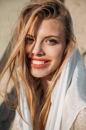 attractive blonde cheerful girl in white silk scarf looking at camera