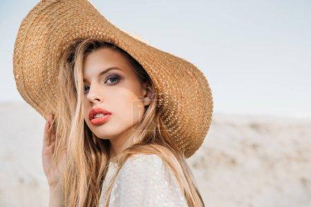 attractive blonde girl posing in trendy straw hat