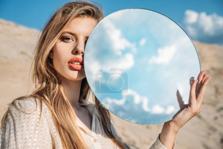 attraktives elegantes Modell mit rundem Spiegel mit Reflexion des bewölkten Himmels