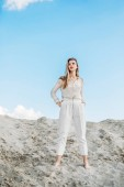 attractive fashionable woman in white clothes posing on sand dune