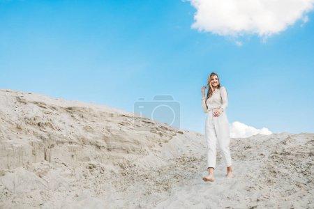 belle femme en blancs vêtements à la mode, posant sur une dune de sable avec un ciel bleu
