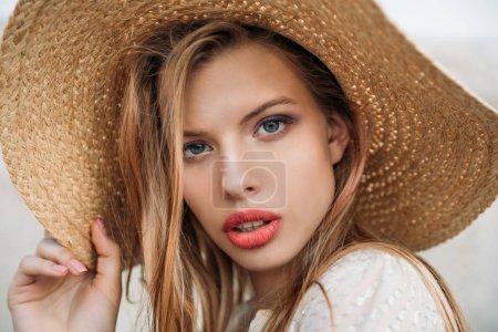 beautiful fashionable girl posing in straw hat